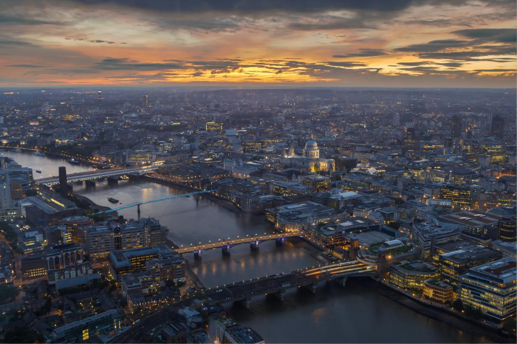 An aerial photo of London showing part of the River Thames with St Pauls in the middle ground. Taken at sunset.